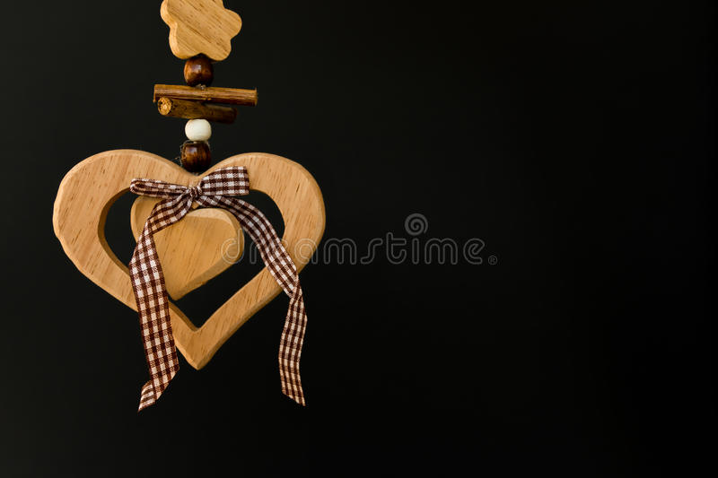 Wooden heart on a rope with wooden balls, a bow in the middle, s stock images