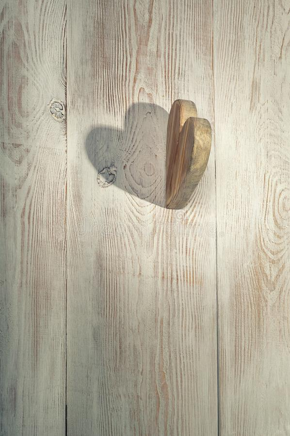 Wooden heart and shadow. Valentine`s day background. Wooden tabl stock photo