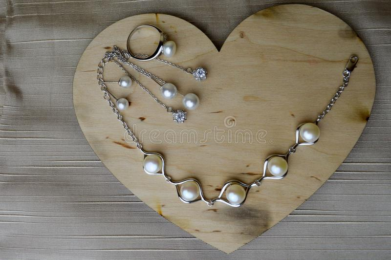 A wooden heart for Valentine`s Day with silver ornaments with pearls and diamonds royalty free stock photo