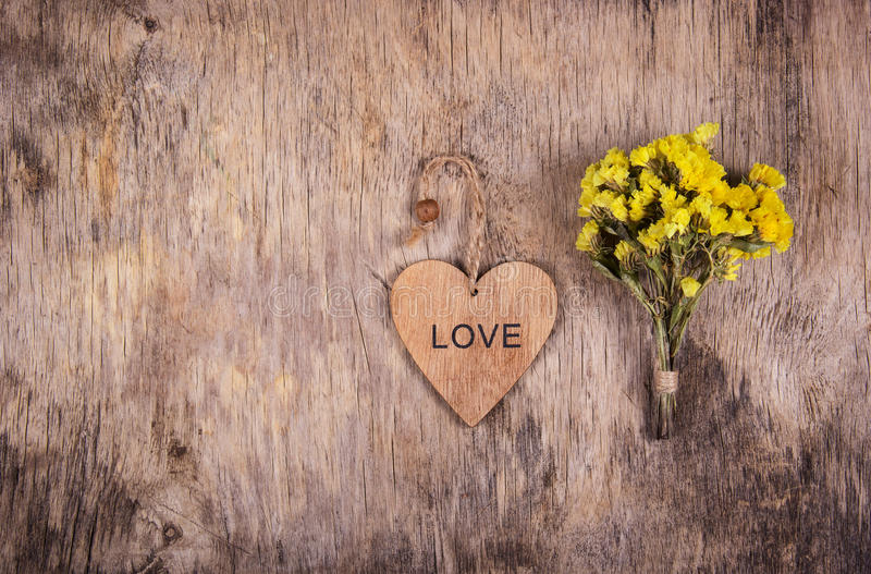Wooden heart and yellow flowers on an old worn wooden background. Backgrounds and textures. Copy space stock images