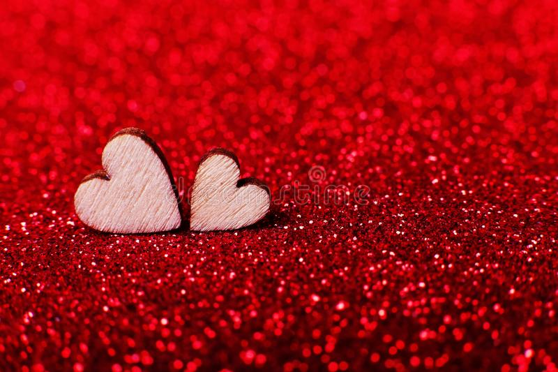 Wooden hearts on brilliant red bright background for a festive decoration. Copy space. stock photo