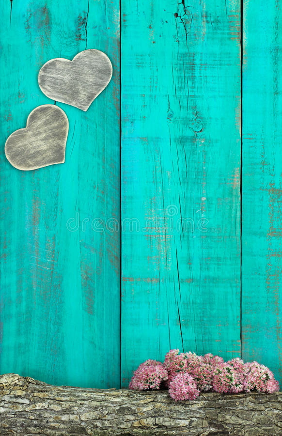 Wooden Hearts Hanging On Antique Teal Blue Fence With Log