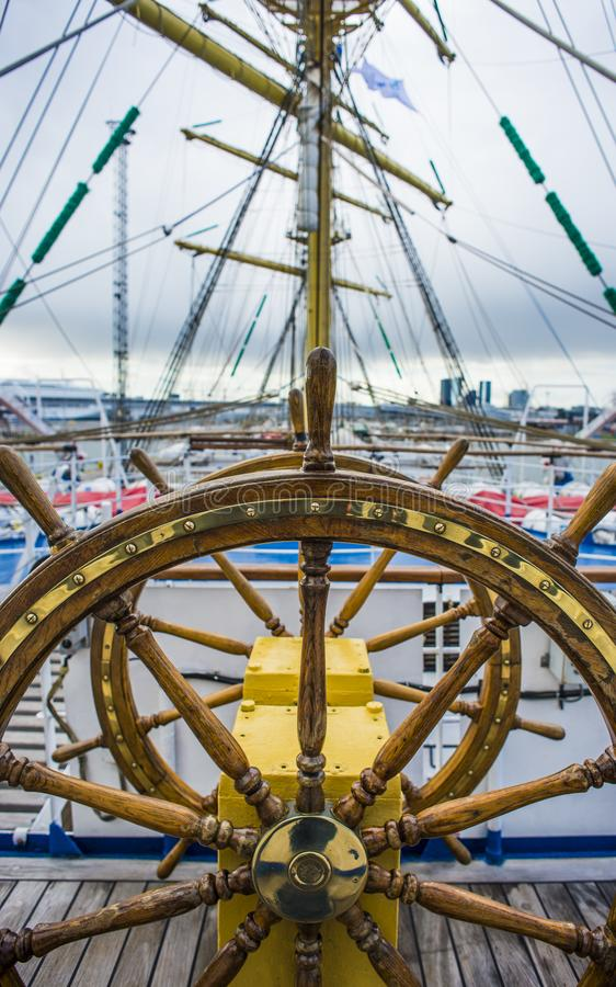 Wooden helm wheel with copper parts on a sailing ship. royalty free stock image