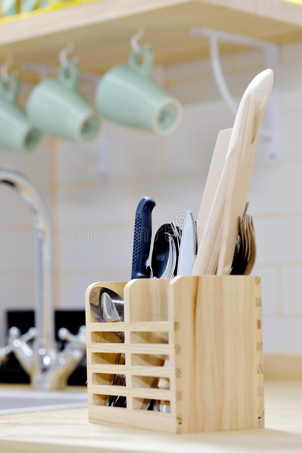 Wooden holder organizer for kitchen tools utensils spoons, knives and spatula on countertop in the modern kitchen stock images