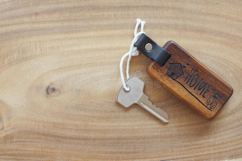Wooden home keyring with house skeleton key on light wooden floor. Welcome to new home concept. Copy space stock photos