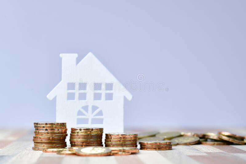 Wooden home and stack money coins of property investment concept royalty free stock photo