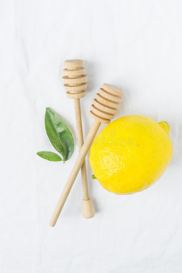 Wooden Honey Dippers Ripe Yellow Lemon Green Citrus Leaves on White Cotton Linen Fabric Background. Organic Cosmetics. Ayurveda Healthy Lifestyle Concept. Copy royalty free stock photo