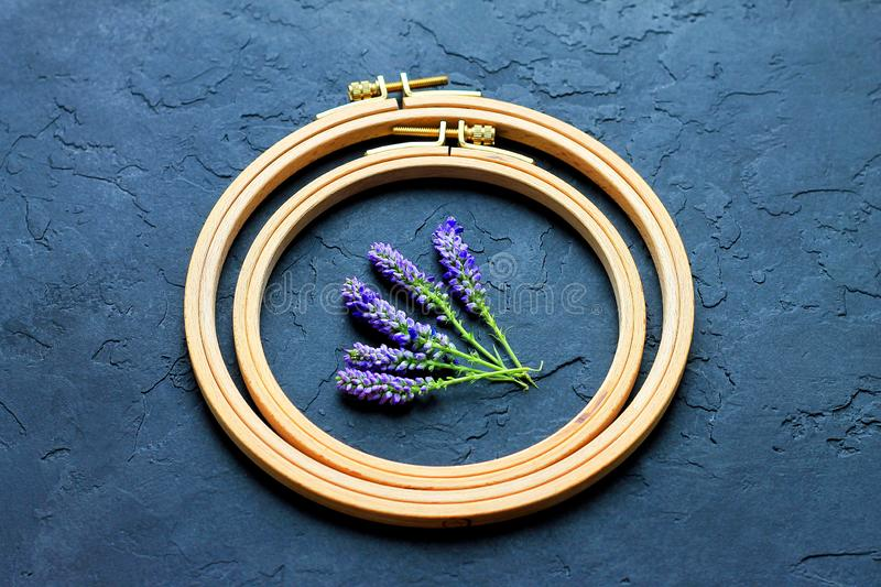 Wooden hoop on a dark background inside the hoop are blue flowers stock photo