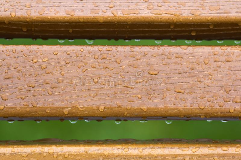 Wooden horizontal planks, boards, garden park bench back with transparent rain water drops on background of green fresh grass. stock image