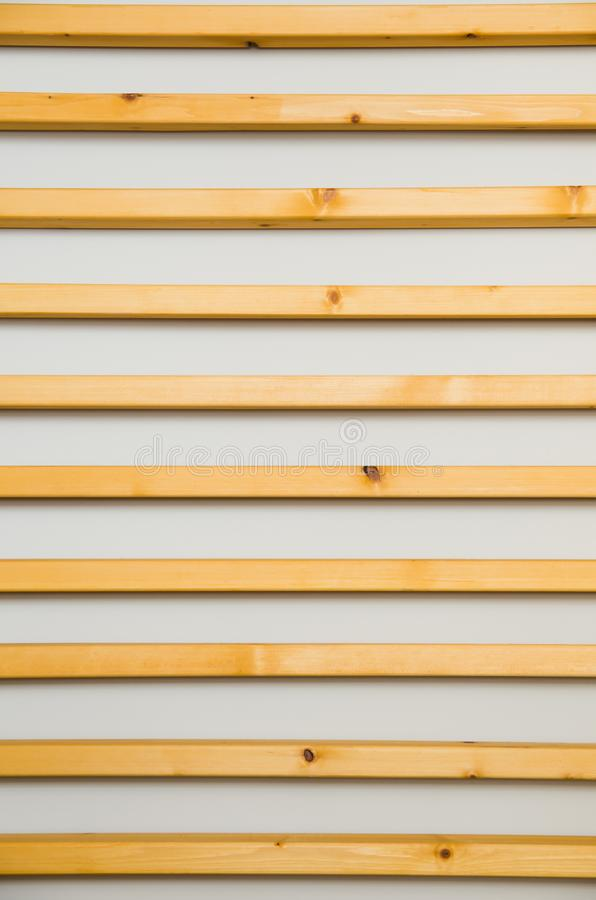 Wooden horizontal slats batten on a light gray wall background. Interior detail, texture, background. The concept of minimalism an. D Scandinavian style in the stock photos
