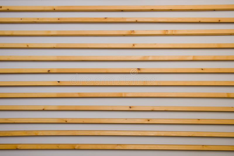 Wooden horizontal slats batten on a light gray wall background. Interior detail, texture, background. The concept of minimalism an. D Scandinavian style in the royalty free stock images