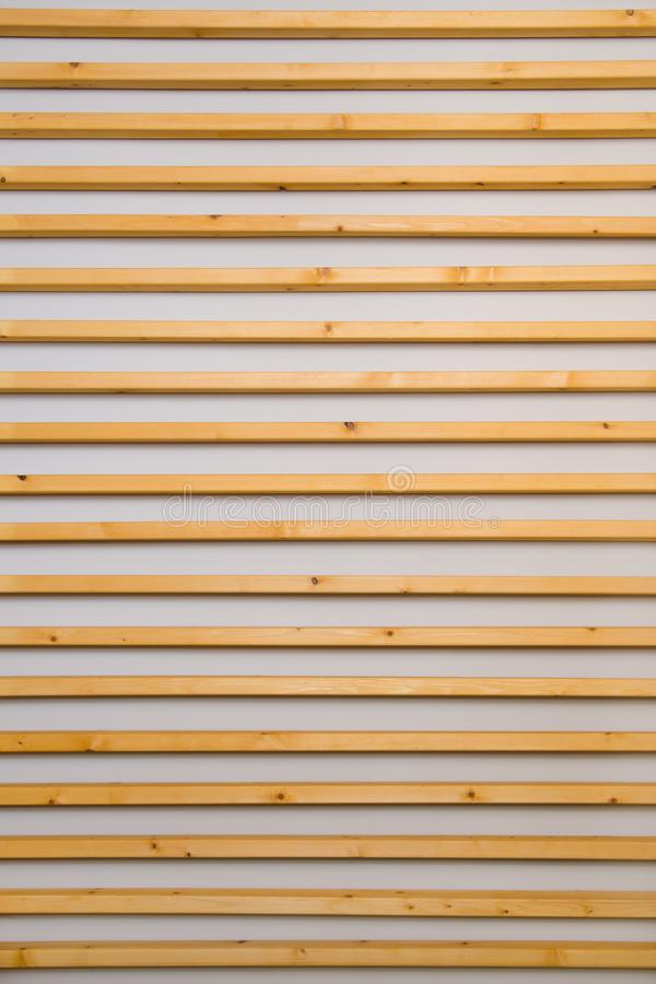 Wooden horizontal slats batten on a light gray wall background. Interior detail, texture, background. The concept of minimalism an. D Scandinavian style in the royalty free stock photo