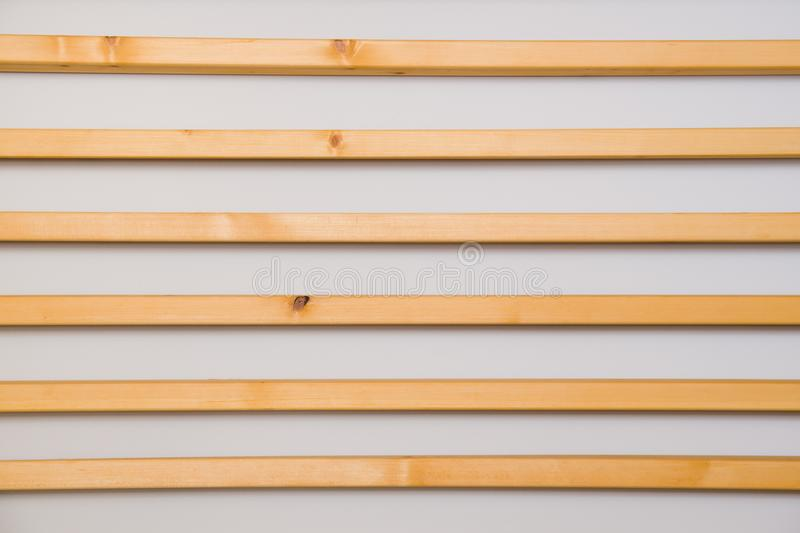 Wooden horizontal slats batten on a light gray wall background. Interior detail, texture, background. The concept of minimalism an. D Scandinavian style in the stock image