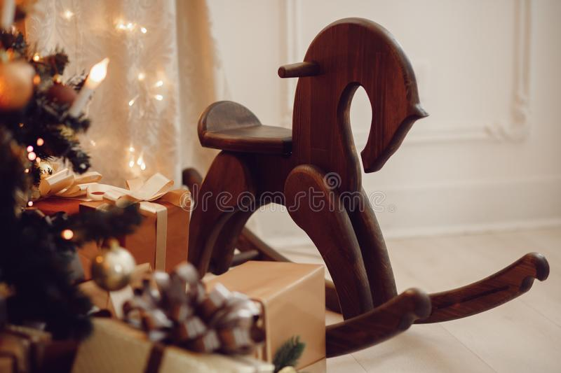 Wooden horse toy under Christmas tree surrounded by gifts royalty free stock photo