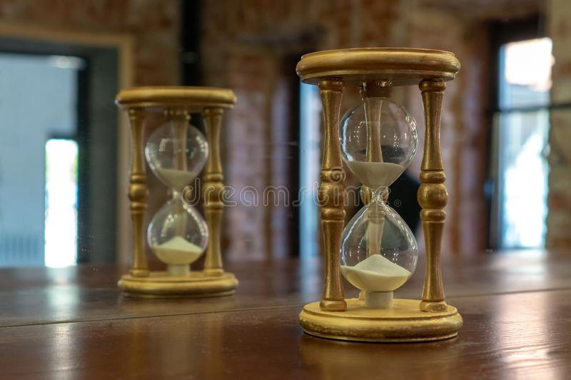 Wooden hourglass reflected in the mirror. Hourglass on a brown table royalty free stock photos