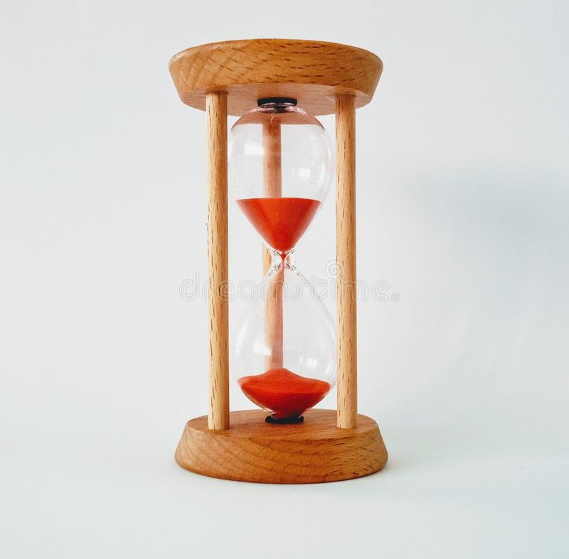 Wooden hourglass on white background with red sand stock photography