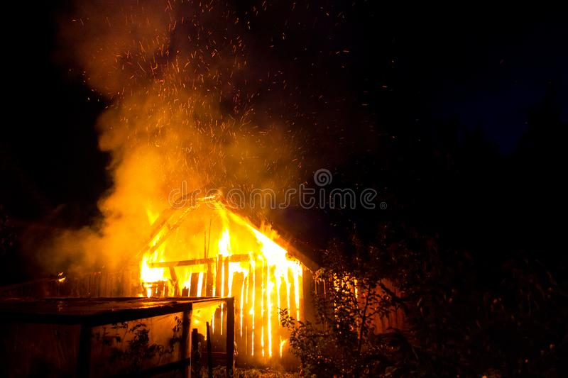 Wooden house or barn burning on fire at night.  stock photography