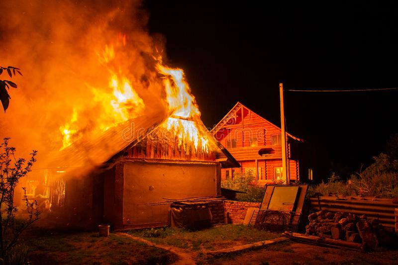 Wooden house or barn burning on fire at night.  stock image
