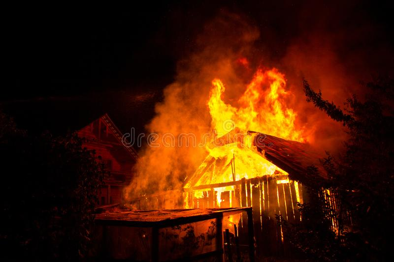 Wooden house or barn burning on fire at night.  royalty free stock images