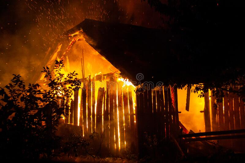 Wooden house or barn burning on fire at night.  royalty free stock photos