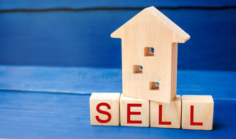 Wooden house on a blue background with the inscription sell. sale of property, home, real estate. affordable housing. place for te. Xt. copy space stock photo