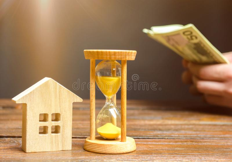 Wooden house and clock. Businessman counting money. Payment of deposit or advance payment for renting a home or apartment. Long-. Term mortgage on the house. Tax royalty free stock photos