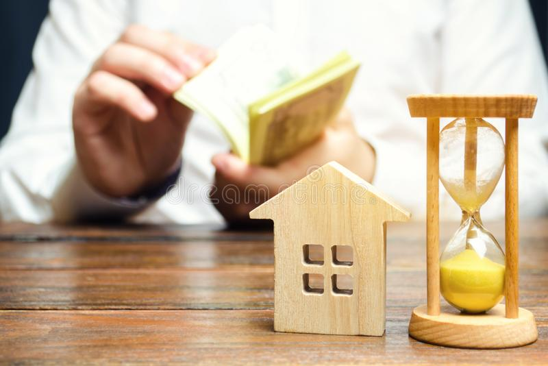 Wooden house and clock. Businessman counting money. Payment of deposit or advance payment for renting a home or apartment. Long-. Term mortgage on the house. Tax stock photography