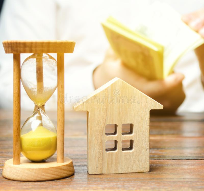 Wooden house and clock. Businessman counting money. Payment of deposit or advance payment for renting a home or apartment. Long-. Term mortgage on the house. Tax royalty free stock image