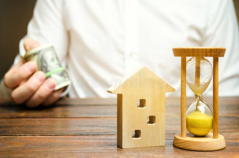 Wooden house and clock. Businessman holds money. Payment of deposit or advance payment for renting a home or apartment. Long-term. Mortgage on the house royalty free stock photos