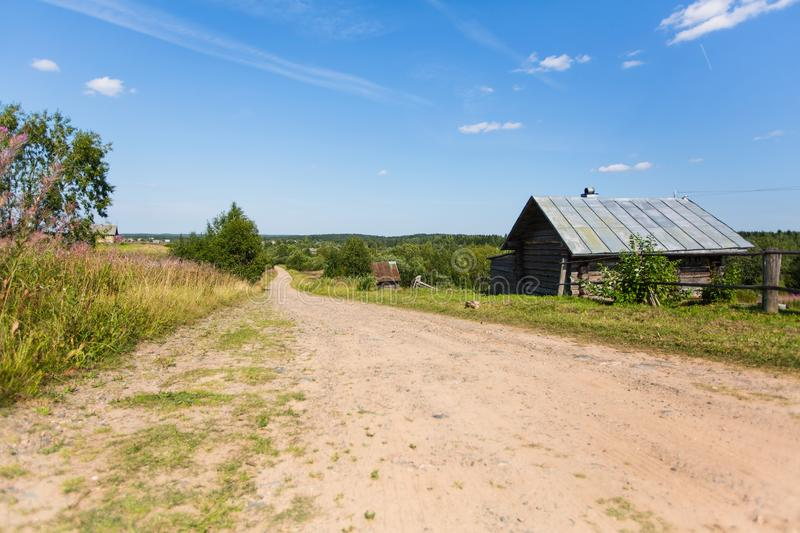 Wooden house and country road, rural landscape. Remote village in Karelia Republic royalty free stock photos