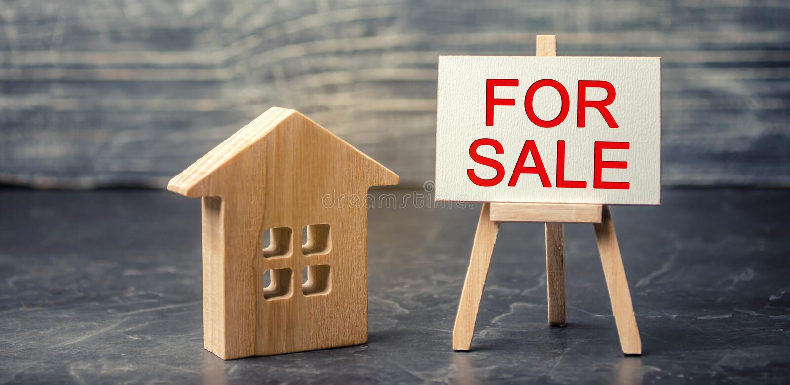 Wooden house and dollars with the inscription `for sale`. sale of property, home. affordable housing. sale of apartments. real est. Ate agent services. realtor stock photography