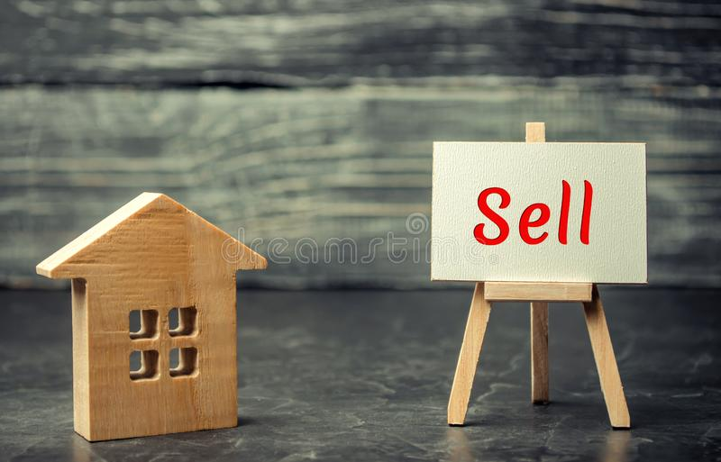 Wooden house and dollars with the inscription `sell`. sale of property, home. affordable housing. sale of apartments. real estate. Agent services. realtor stock photography