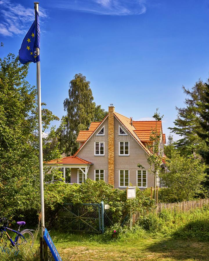 Wooden house with Europe flag on the island Hiddensee. Home, holiday, timber, tree, cottage, summer, building, architecture, fence, blue, nature, travel stock photos