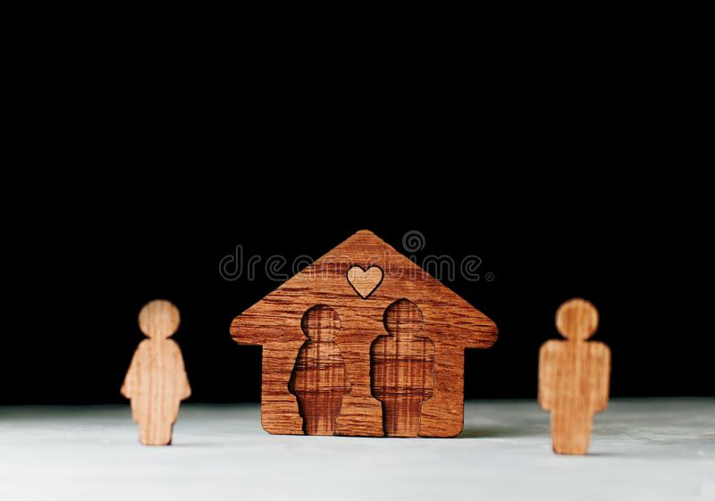 Wooden house with figures of man and woman on black background. As symbol of problems in family relationships. Focus on house, blank space for text stock photo