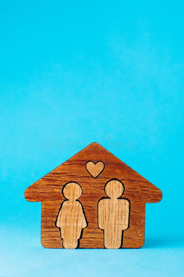 Wooden house with figures of man and woman on blue background wi stock image