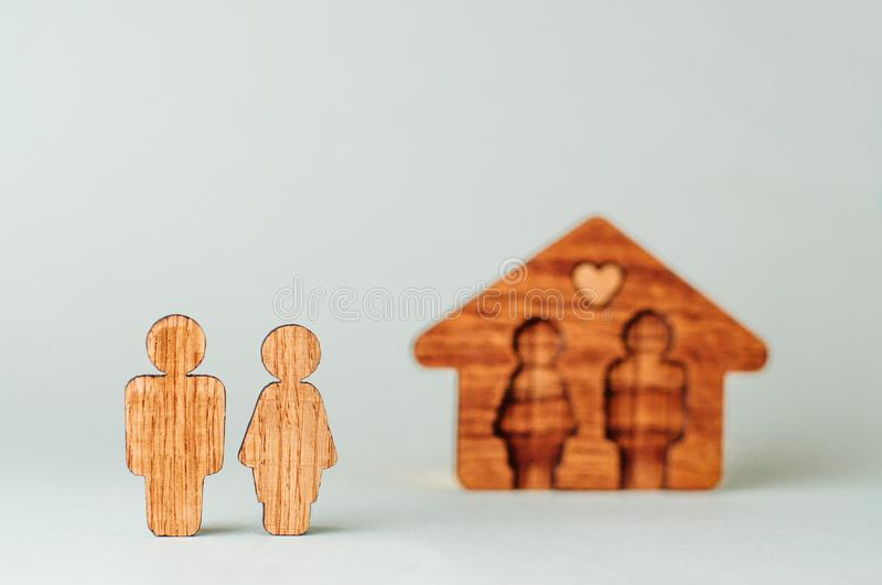 Wooden house with figures of man and woman inside on grey background. With blank space for text stock image