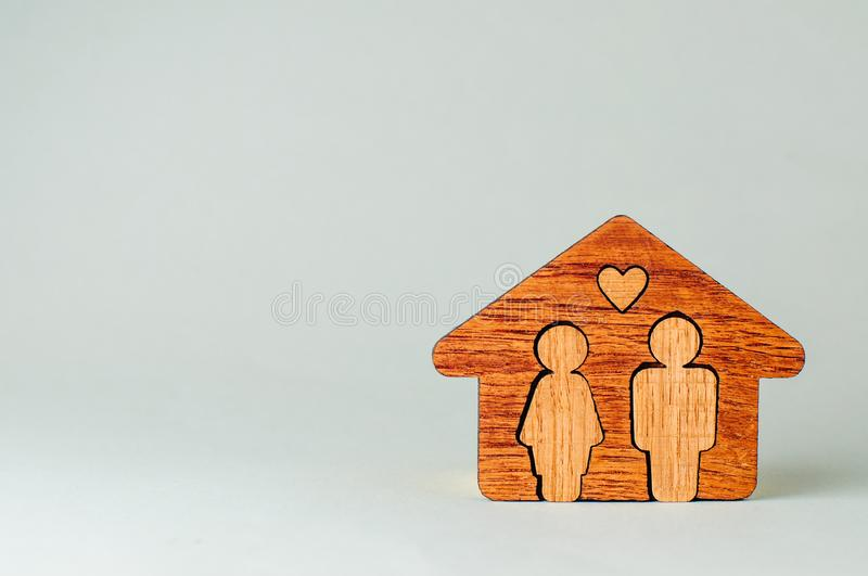 Wooden house with figures of man and woman inside on grey background. With blank space for text royalty free stock images