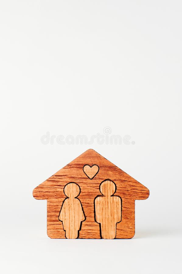 Wooden house with figures of man and woman inside on white background. With blank space for text stock photography