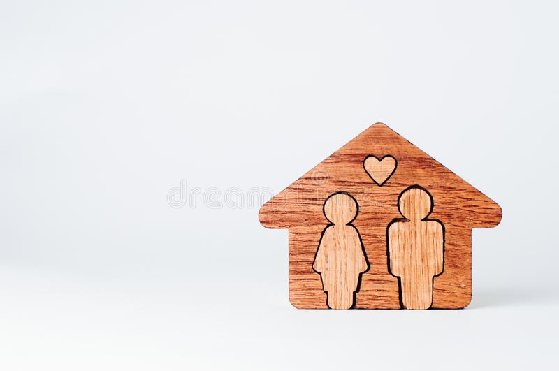 Wooden house with figures of man and woman inside on white background. With blank space for text stock image