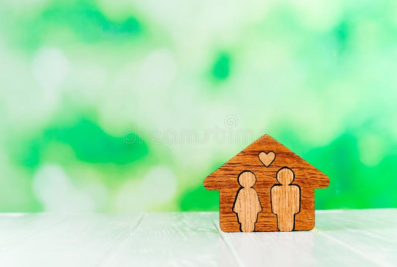 Wooden house with figures of man and woman inside on white background. Family home concept. Wooden house with figures of man and woman inside on white background stock images