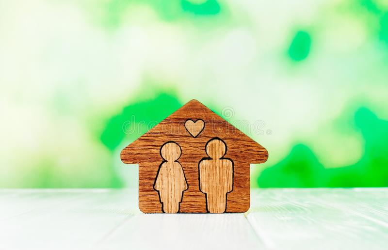 Wooden house with figures of man and woman inside on white background. Family home concept. Wooden house with figures of man and woman inside on white background stock photos