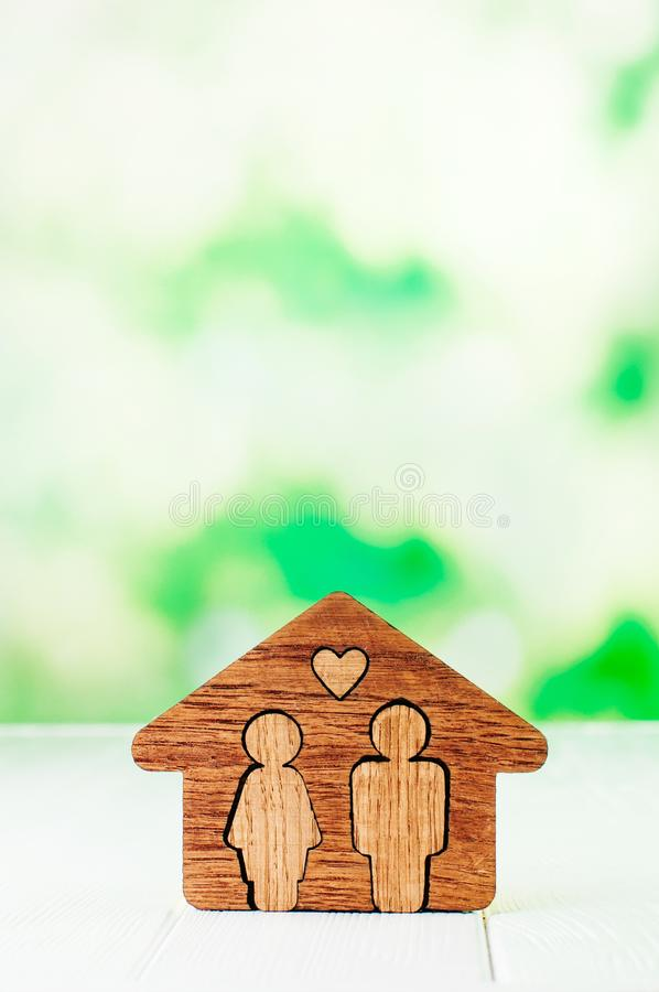 Wooden house with figures of man and woman inside on white background. Family home concept. Wooden house with figures of man and woman inside on white background royalty free stock image