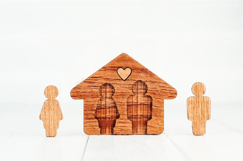 Wooden house with figures of man and woman on white background. Family home concept. Wooden house with figures of man and woman on white background with blank stock photos