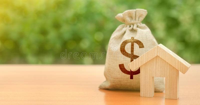 Wooden house figurine and a dollar money bag. Family budget, control and reduction of expenses. subsidized funds. Mortgage loan stock images