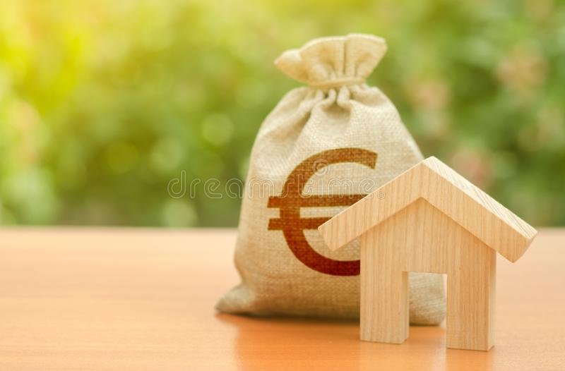 Wooden house figurine and Euro money bag on the background of nature. Budget, subsidized funds. Mortgage loan for the purchase stock images