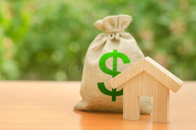 Wooden house figurine and money bag on the background of nature. Mortgage loan for the purchase of housing, construction or royalty free stock images
