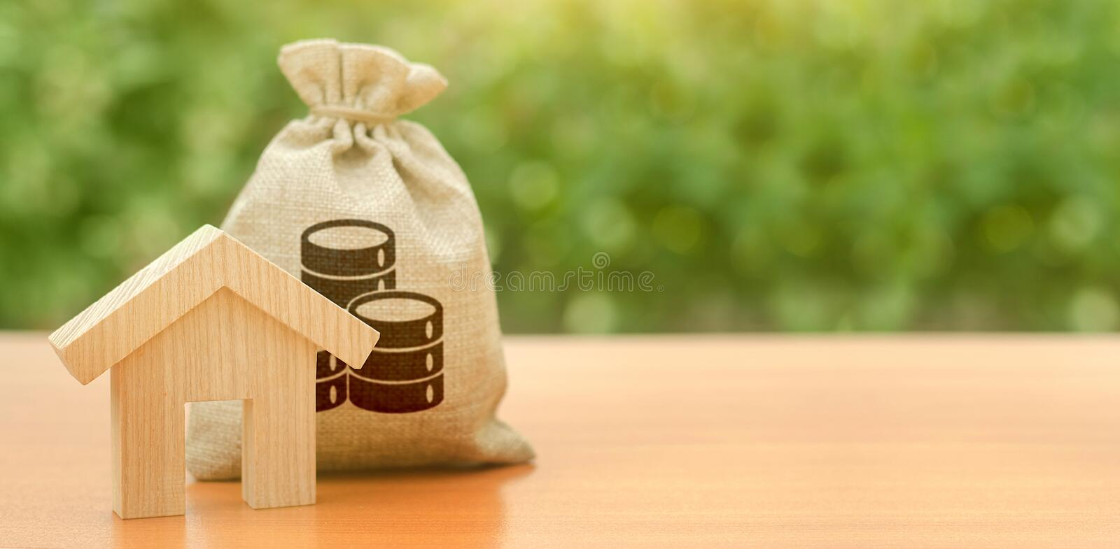 Wooden house figurine and a money bag. Family budget, control and reduction of expenses. subsidized funds. Mortgage loan stock photography