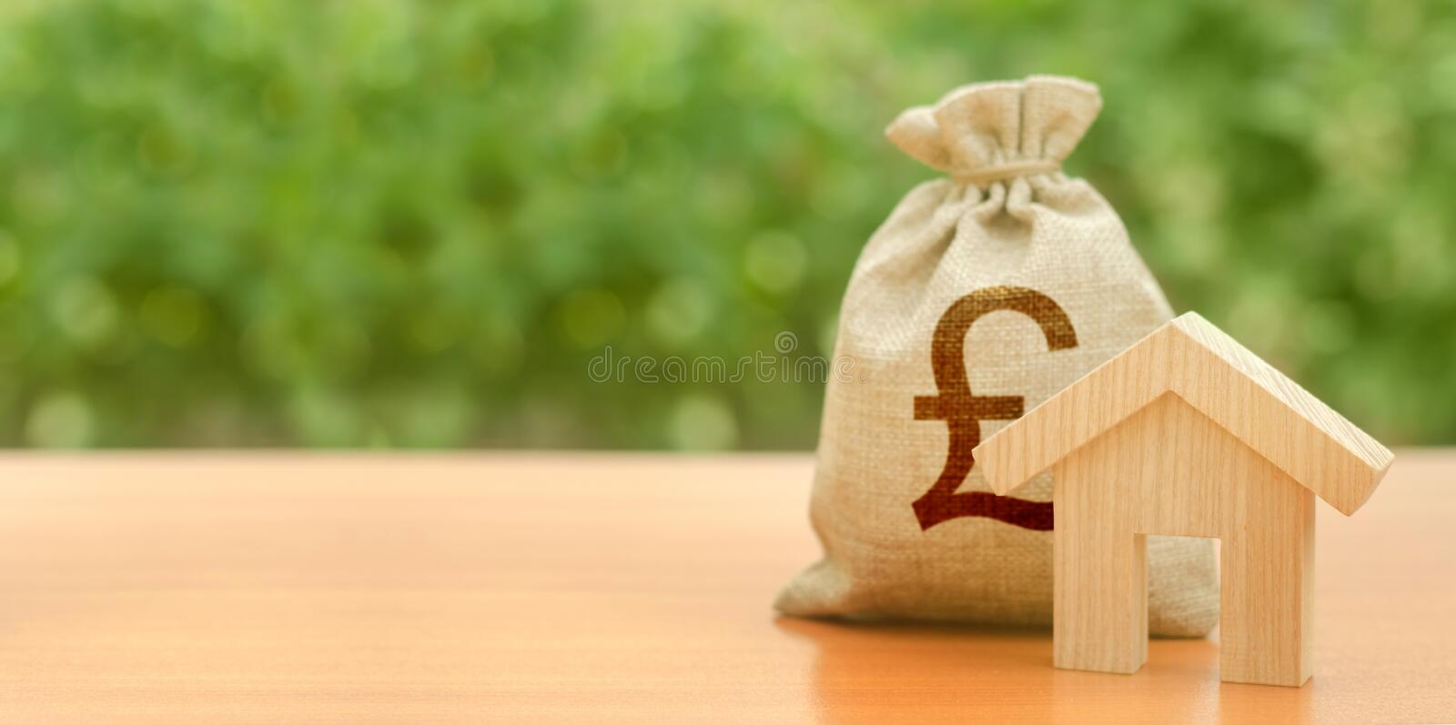 Wooden house figurine and pound sterling money bag on the background of nature. Budget, subsidized funds. Mortgage loan royalty free stock photography