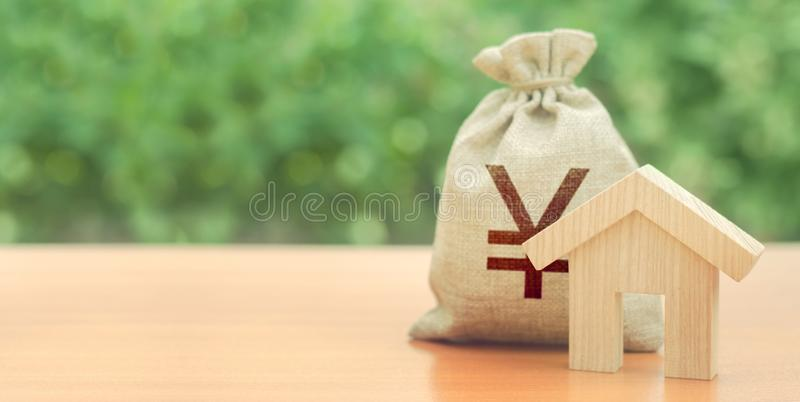 Wooden house figurine and Yen or yuan money bag. Budget, subsidized funds. Mortgage loan for purchase housing, construction or stock image