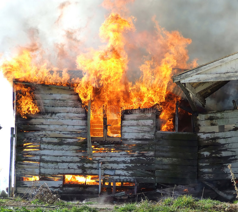Wooden house on fire stock photos